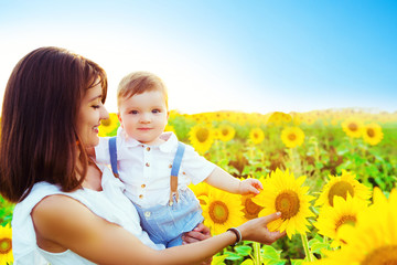 Loving mother holding son in her arms in rest on sunflowers field. Nature and summer