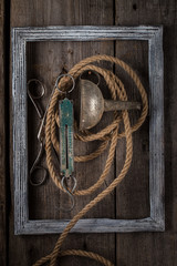 Old scissors and rope hanging on a wooden wall.