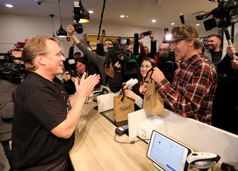 Canopy Growth CEO Bruce Linton applauds after handing Ian Power and Nikki Rose, who were first in line to purchase the first legal recreational marijuana after midnight, their purchases at a Tweed retail store in St John's
