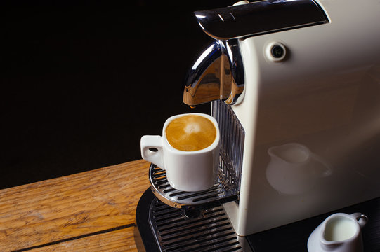 Coffee machine with cup of coffee  Espresso machine making coffee with capsules background on wood