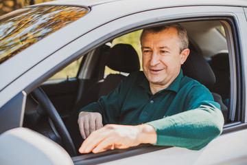 Portrait Of A Happy Mature man Driving Car To Go To Work or travels. Concept of automobile and popular hobby