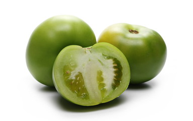 Fresh green tomato sliced in half, isolated on white background