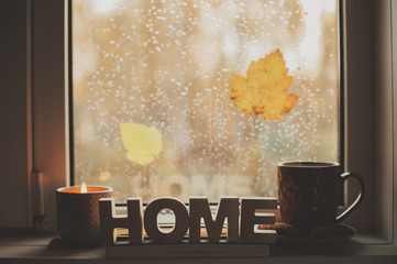 cozy autumn morning at home. Hot tea and candle on window in rainy cold day. Spending holidays at home.