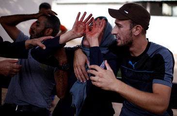 The mother of a Palestinian, who was killed in an Israeli air strike, reacts as her hands are stained with his blood, at a hospital in the northern Gaza Strip