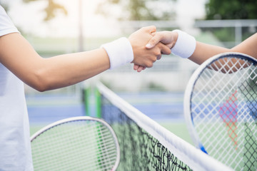 Women tennis player handshaking after playing a tennis match. Handshake at tennis court - agonism,respect,fair play,sport concept.