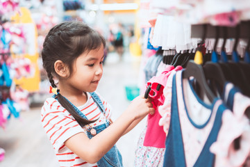 Cute asian child girl choosing dresses in clothes department in supermarket