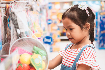 Cute asian child girl choosing the toy and shopping in supermarket