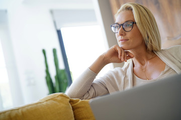 Blond woman relaxing in sofa, connected with laptop