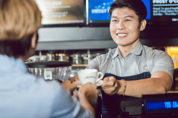 Portrait of young smiling barista serving coffee to female customer in the coffee shop