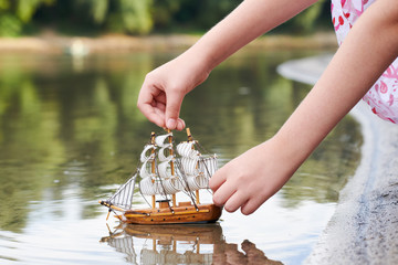 girl playing with a toy sailing ship by the river, hand closeup