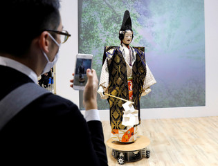 A man takes a picture of SEED Solutions' humanoid robot performing the classical Japanese musical drama Noh during its demonstration at World Robot Summit in Tokyo