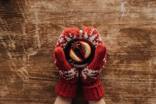cropped image of woman in mittens holding glass of mulled wine at wooden tabletop, christmas concept