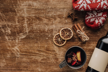 top view of mulled wine in cup and wine bottle on wooden tabletop, christmas concept