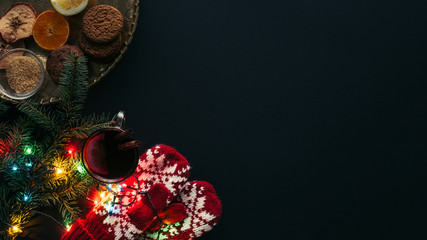 elevated view of cup of mulled wine, garland, mittens and cookies isolated on black, christmas concept
