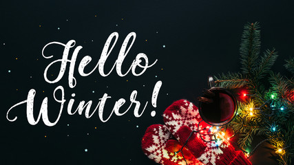 elevated view of mulled wine in cup, garland and greeting Hello Winter isolated on black, christmas concept
