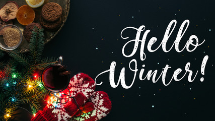 top view of mulled wine in cup, garland and greeting Hello Winter isolated on black, christmas concept