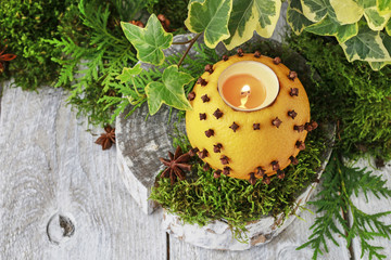 Orange pomander ball with candle on wooden table.