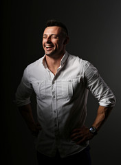 Attractive business man laughing with wide opened mouth and sporty biceps arms in white style shirt on dark shadow background. Closeup portrait.