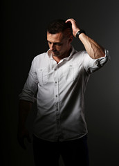 Confident attractive serious businessman thinking and scratching the head in white style shirt on grey dark shadow background. Closeup portrait.