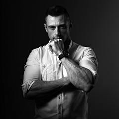 Strong serious business man thinking with sporty biceps arms in white style shirt on grey dark shadow background. Closeup motivation concept portrait. Black and white