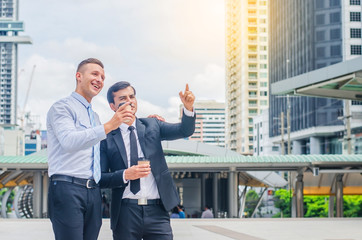 Two business people with coffee chatting and pointing up while showing office to colleague in the morning at outdoor covered walkway