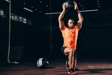 handsome athletic bodybuilder performing lunge with medicine ball overhead in dark gym