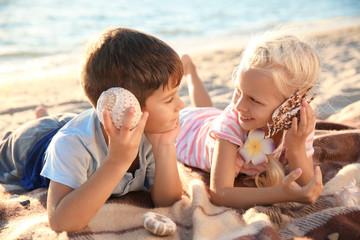Cute little children with sea shells on beach