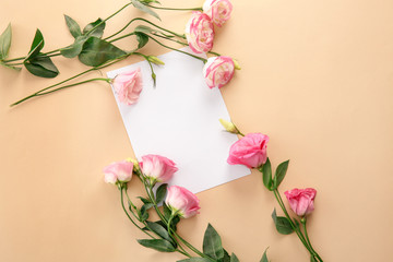 Composition with blank greeting card and beautiful flowers on color background
