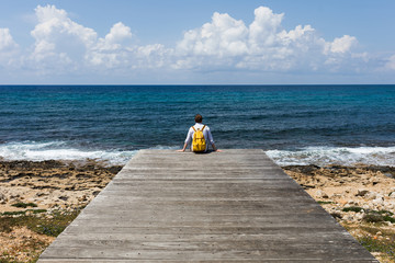 Tourist traveler guy stands on a wooden pier in solitude and looks at the blue sea, ocean. Calm and peace. Yellow backpack. The coast and a sandy beach with stones. Travel and vacation with a hike.