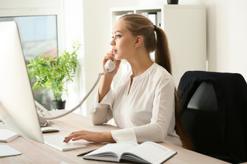 Beautiful female secretary talking on telephone in office