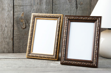 Two empty picture frames on wooden background.