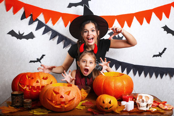 Funny Mother and daughter having fun at home. Happy family preparing for Halloween. People wearing carnival costumes.