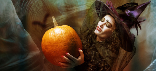Halloween Witch with Pumpkin Beautiful young woman in witches hat and costume