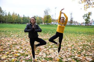 Autumn photo of sporty women doing yoga in forest at morning against background of trees.