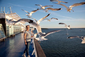 Older woman watching seagulls flying. Photo of a middle aged lady on the cruise ship deck in a Baltic Sea cruise.