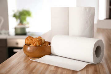 Rolls of paper towels with tasty pastry on kitchen table