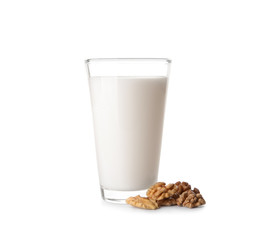 Glass of milk and walnuts on white background