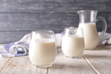 Glasses of milk on wooden table