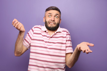Portrait of confused man on color background