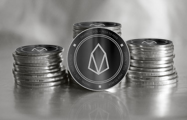 EOS digital crypto currency. Stack of black and silver coins. Cyber money.