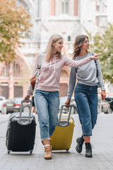 female tourists with backpacks and baggage walking on city street