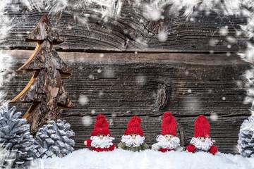 4 Weihnachtsmänner im Advent vor Holzwand, Schnee