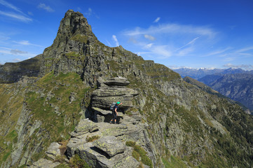 Fotomurales - Female hiker on a narrow ridge in the Ticino mountains. Via Alta Verzasca, Switzerland.
