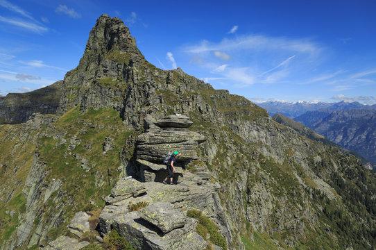Female hiker on a narrow ridge in the Ticino mountains. Via Alta Verzasca, Switzerland.
