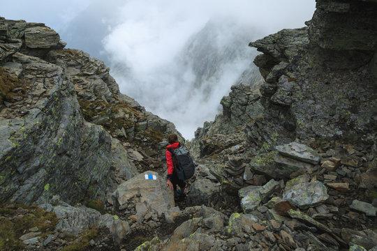 Female hiker descending a mountain on the Via Alta Verzasca in Ticino, Switzerland.
