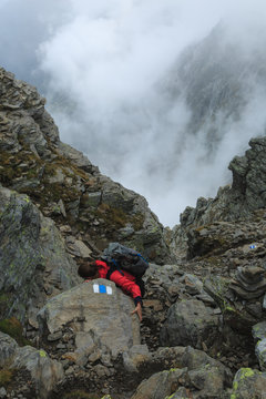 Female hiker climbing down on the steep route of the Via Alta Verzasca in Ticino, Switzerland.