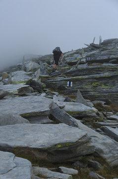 Female hiking into the clouds on a mountain ridge, hiking the Via Alta Verzasca in Ticino, Switzerland.