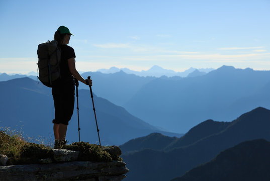 Female hiker enjoying the morning view in the Ticino mountains. Via Alta Verzasca, Switzerland.