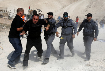 Israeli policeman grabs an activist in the Palestinian Bedouin village of Khan al-Ahmar that Israel plans to demolish, in the occupied West Bank