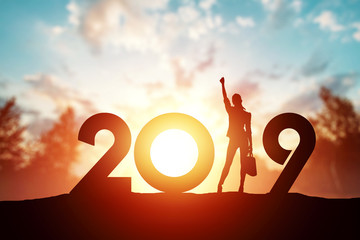 Creative background, Silhouette young woman Enjoying on the hill and 2019 years while celebrating new year. Happy New Year 2019, copy space.